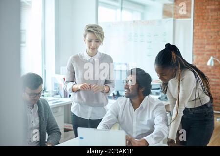 equipo activo que orginiza conferencia en línea en la sala de oficina con una pared de cristal. foto de cerca.