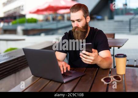 La mano del hombre usando el teléfono inteligente en el café interior moderno de la calle, el hombre de negocios ocupado usando el teléfono celular y las tecnologías en línea Foto de stock