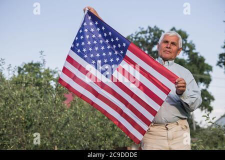 El patriótico anciano celebra el día de la independencia de los estados unidos el 4 de julio con una bandera nacional en sus manos. Día de la Constitución y la Ciudadanía. Gran Nacional