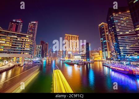 Dubai Marina por la noche con rascacielos, barcos y reflexiones en el agua, Emiratos Árabes Unidos
