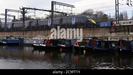 Un tren Javelin pasa por los barcos del canal amarrados en el Canal de Regent cuando sale de la estación de Saint Pancras en Londres