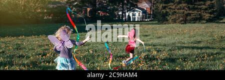 Niños niñas jugando con cintas en el parque. Niños corriendo en el prado juntos. Actividades al aire libre en el patio trasero de verano. Feliz infancia candid auténticos lifes