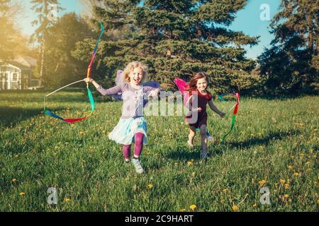 Niños felices niñas jugando con cintas en el parque. Unos niños adorables corriendo en el prado jugando juntos. Actividades al aire libre en el patio trasero para niños. H