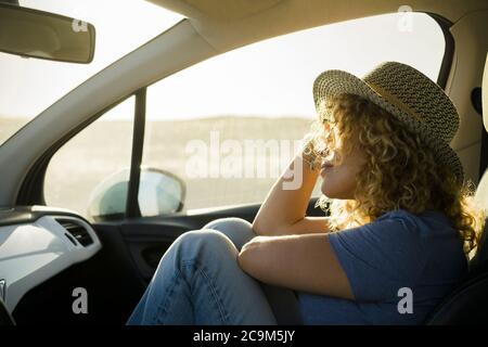 una, hermosa mujer rizado disfrutando de sus vacaciones al aire libre viajando con un coche - puesta de sol y día soleado en el fondo - persona relajada y serena
