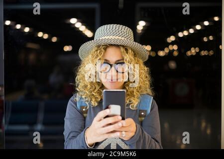 retrato y primer plano de hermosa mujer rizado y rubia mirando la cámara sonriendo - gente feliz viajando en el aeropuerto - vacaciones al aire libre