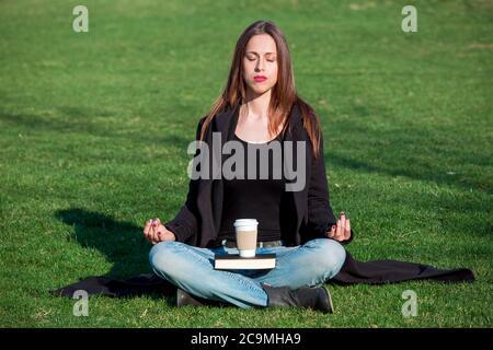 la chica se sienta con los ojos cerrados en la posición de loto y medita en la hierba en el parque en un día soleado, en un abrigo negro y jeans azules en ella