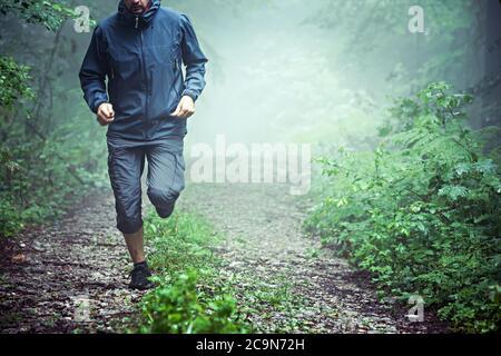 Primer plano de atleta masculino, vestido de ropa al aire libre, corriendo a través de bosque brumoso temprano en la mañana. Espacio de copia disponible. Foto de stock