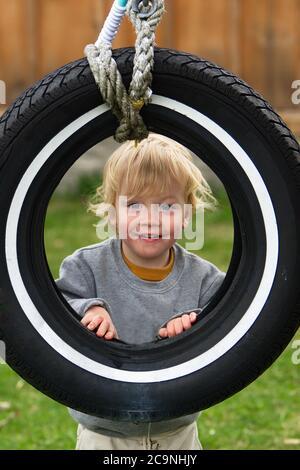 Adorable rubia chico mirando a través de la rueda swing
