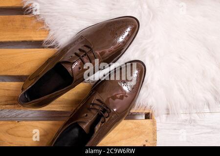 Zapatos de piel de patente marrón en un pallet, piel blanca. Concepto de moda