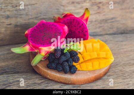 Fruta de dragón y mango en rodajas sobre un viejo fondo de madera