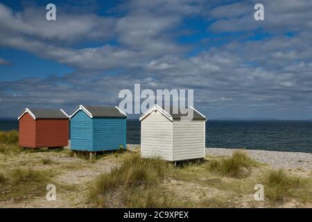 Coloridas cabañas de playa de color azul y blanco en Findhorn Beach, Moray Coast, Escocia
