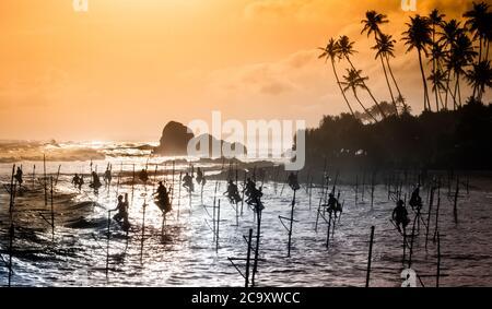 Pescadores tradicionales al atardecer cerca de Koggala en Sri Lanka
