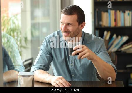 Hombre feliz mirando hacia fuera, hay una ventana sentada en una mesa de la cafetería que sostiene un vaso