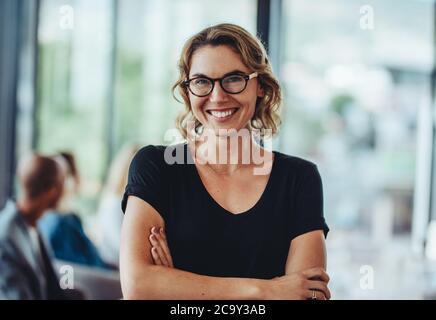 Retrato de exitosa mujer profesional con sus brazos cruzados. Mujer de negocios sonriente de pie en la oficina y mirando la cámara. Foto de stock