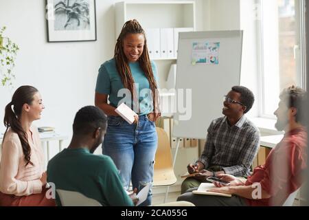 Grupo multiétnico de personas que se sientan en círculo mientras se discute el proyecto de negocios en el cargo, se centran en la sonrisa de la mujer afroamericana hablando con sus colegas, espacio de copia