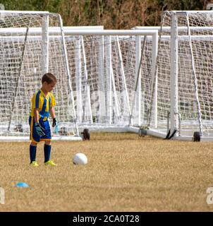 Basingstoke, Hampshire, Reino Unido. Agosto de 2020. Un portero muy joven en entrenamiento con un telón de fondo de redes de meta.