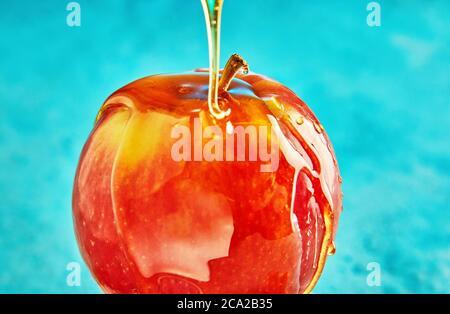 Rosh hashanah - concepto de año Nuevo judío. La miel fluye por una manzana sobre un fondo azul.