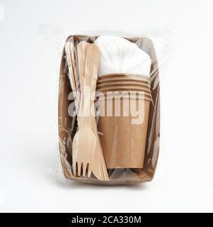 juego de vajilla desechable de papel artesanal en una bolsa de plástico transparente sobre fondo blanco. Concepto de rechazo de plástico, cero residuos.