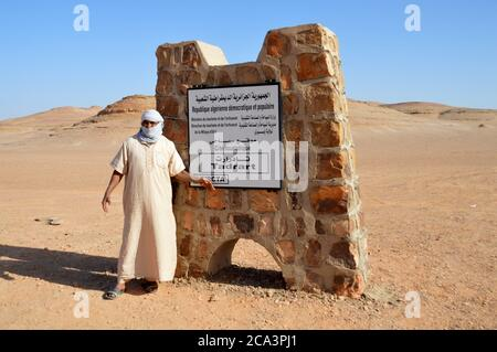 Argelia, Illizi, Tassili N'Ajjer Parque Nacional: Saliendo de la zona de las montañas Tadrart Rouge. Un marcador de frontera, con Tuareg.