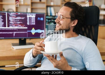 Imagen de un hombre programador alegre y guapo sonriendo y bebiendo café mientras trabajaba en la oficina