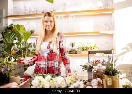 mujer florista componiendo y creando un maravilloso ramo de flores, disfrutar de trabajar en su propia tienda o jardín