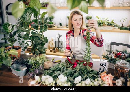 encantadora hermosa mujer joven florista feliz de pie en invernadero lleno de flores y plantas, disfrutar de trabajar con botánica