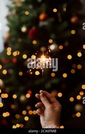 Feliz año nuevo. Quemando sparkler en la mano sobre el fondo de las luces de bokeh de oro en la habitación oscura festiva. Mano sosteniendo fuegos artificiales en el árbol de Navidad con golde