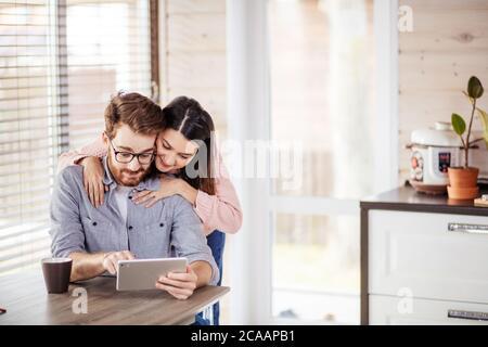 Feliz joven hombre caucásico en espectáculos y mujer en ropa casual con Tablet PC. Edad media emocionada pareja utilizando tablet digital elegir la cocina fu Foto de stock