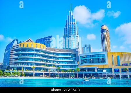 DUBAI, EAU - 3 DE MARZO de 2020: La fachada del centro comercial Dubai Mall con modernos skescrapers y el lago Burj Khalifa en primer plano, el 3 de marzo en Du