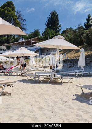 Chalkidiki, Grecia - Julio 30 2020: Limpieza eficaz de la barra de playa para tomar el sol de los muebles para reducir el riesgo de infecciones covid-19. Aplicar solución desinfectante en la superficie de sillas de playa para matar gérmenes y bacterias.