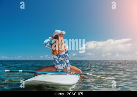 SUP Levántate a la tabla de paletas. Mujer joven navegando en un mar hermoso y tranquilo con agua cristalina. El concepto de un viaje de vacaciones de verano