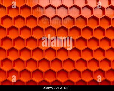 textura hecha de plástico naranja en forma de panales de miel de primer plano, fondo abstracto
