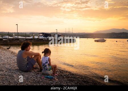 Padre joven e hija pequeña sentada en la playa del lago al atardecer en Manerba del Garda, Lombardía Italia.