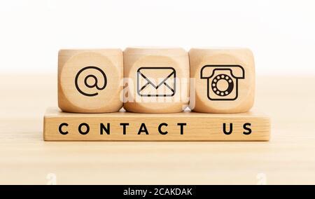 Póngase en contacto con nosotros concepto. Bloques de madera con iconos de correo electrónico, correo y teléfono.Página web Contáctenos o e-mail marketing