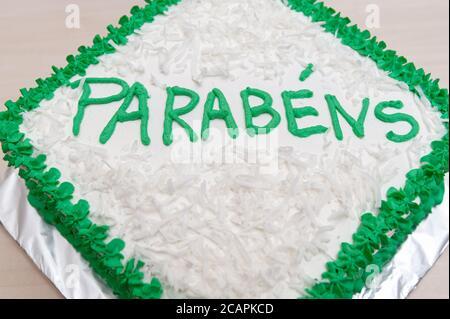 Pastel de cumpleaños decorado con hielo verde y coco rallado. Aislado sobre fondo de mesa de madera. Vista superior. Primer plano.
