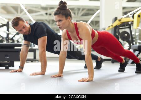 hermosa y fuerte pareja joven haciendo flexiones juntos en el gimnasio. vista lateral