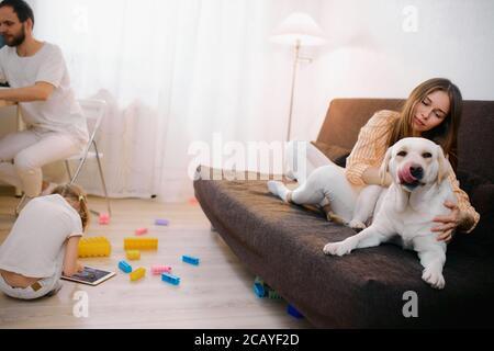 familia amistosa pasar tiempo libre en casa juntos, todo el mundo está ocupado con sus propios intereses, madre jugando con perro mascota, hija pequeña con juguetes
