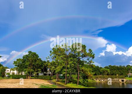 Sarasota, EE.UU., 9 de agosto de 2020. Un arco iris doble bajo la lluvia sobre las residencias Meadows en Sarasota, Florida. Crédito: Enrique Shore/Alamy Stock