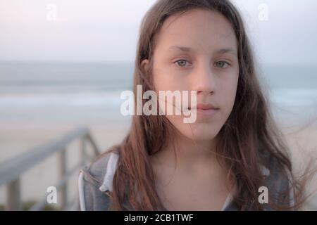 Retrato de una adolescente con pelo largo marrón y ojos verdes mirando la cámara. Mujer joven seria con pelo largo y ondulado.
