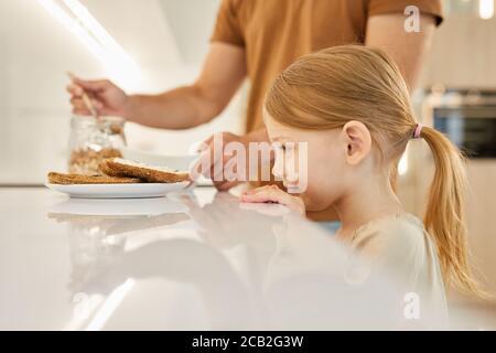 Vista lateral retrato de una linda niña mirando deliciosos sándwiches mientras esperas el desayuno en la cocina, espacio de copiado