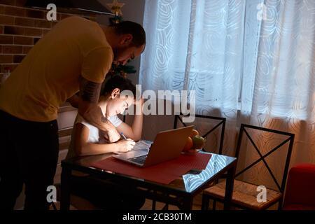 el joven caucásico ayuda a su hijo a estudiar, a hacer tareas en casa, usando un portátil moderno y libros de ejercicios