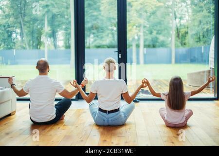 Back of Fit una familia saludable sentada en el loto pose en el suelo en casa. Yoga con niños en casa