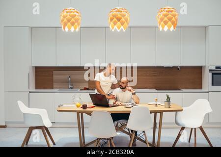 Hombre concentrado trabajando en casa usando un ordenador portátil. Siéntate a la mesa en la cocina, la mujer lo apoya junto al hombre. Casa interior blanca