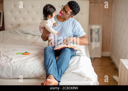 Un hombre africano divertido y guapo disfruta pasando tiempo con un niño, compartiendo con el conocimiento y la experiencia