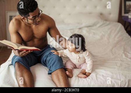 hermosa niña escuchando a papá leyendo cuento de hadas mientras descansaba en el dormitorio. foto de cerca, espacio de copia, interés, estilo de vida