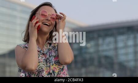 Chica sonriente en gafas de sol de moda hacer una llamada en el teléfono móvil. Puesta de sol. Bonita mujer turística de verano cerca de la terminal del aeropuerto. Look de estilo hawaiano. Uso del smartphone para tomar. Vacaciones, turismo Foto de stock