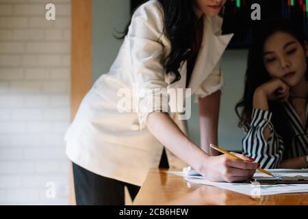 Gente de negocios que se reúne en la oficina y que discute sobre un documento, dos mujeres con un informe financiero con compañero de trabajo en el ordenador portátil