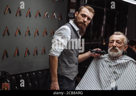 Peluquería profesional haciendo diseño de barba, recortar el vello con maquinilla eléctrica. Salón de belleza. La belleza masculina. El cliente es un maduro gentlem respetable