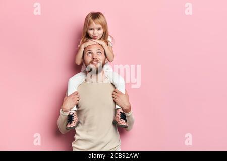 jóvenes buenos pareciéndose bondadosa diversión con su hijo pequeño, retrato de cerca, fondo rosado aislado, disparo de estudio. familia, paternidad feliz