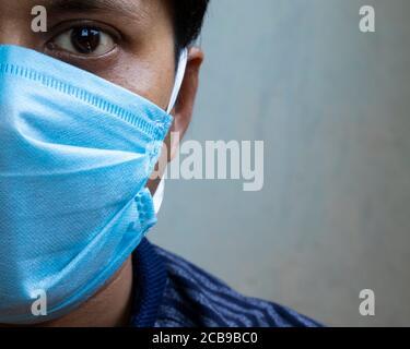 Disparo en la cabeza de un hombre indio con mascarilla quirúrgica de la nariz mirando la cámara para la protección del virus de corona o covid-19